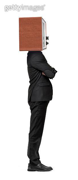An isolated businessman stands in a side view with crossed arms and a TV box instead of his head