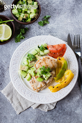 Grilled chicken breast with tomato and pepper grill and salsa from avocado and cucumber on plate on stone gray table background. Healthy Clean Diet Dinner Concept. Top view, copy space