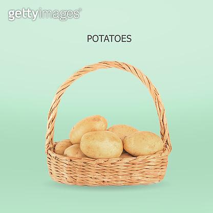 Potatoes in wicker basket on green backgroun