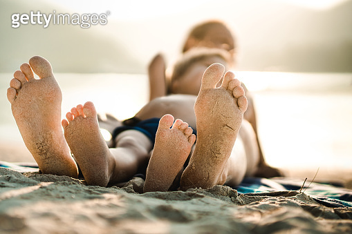 Close up of sandy feet of a mother and son on the beach.