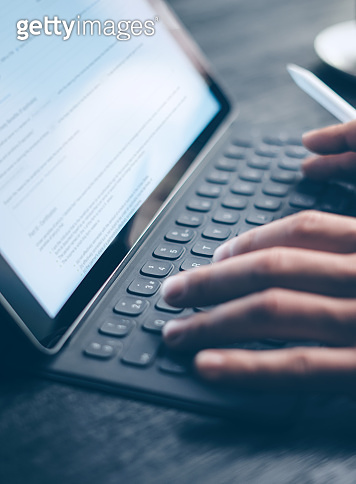 Closeup view of male hands typing on electronic tablet keyboard-dock station. Business text information on device screen. Man working at office.Vertical,cropped.
