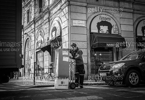 Worker unload  big boxes using the Hand truck on the italian street in Milan, Italy