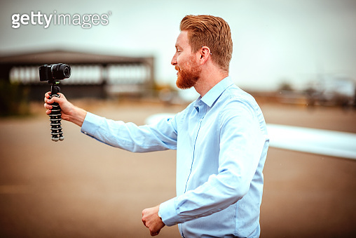 Rich young man shooting a video blog on an airport runway