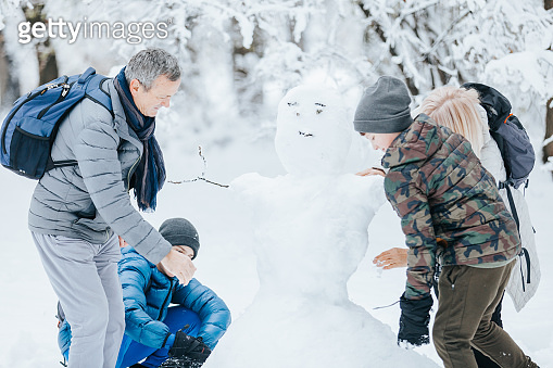 Family Playing Outside at the Park Making Snowman