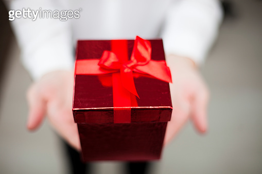 Female Hands Holding a Red Gift Box
