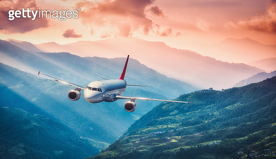 Aircraft is flying over green hills and mountains against colorful red sky with clouds at sunset. Landscape with passenger airplane, beautiful sky, village. Aircraft. Business travel. Commercial plane