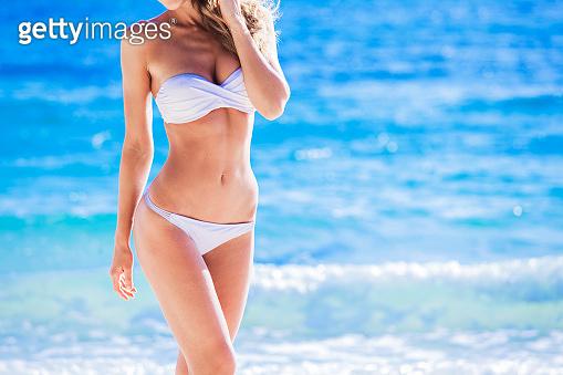 Tanned woman body in white bikini