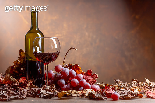 Glass and bottle of red wine on a table with grapes .