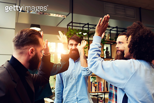 Skilled male coach using teambuilding concept to motivate employee for collaboration and development starting day with morning high-fiving and friendly atmosphere on meeting, standing in coworking