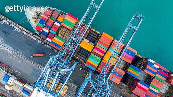 Aerial top view crane shipping container, cargo container ship carrying container import and export business logistic and transportation.