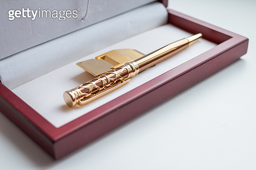 Open gift set. holder clip for money. stationery. wooden present box. golden money clip. A pen in a gift box isolated on white.fountain pen in wooden case made of mahogany, good present idea.business concept