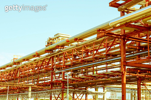 Pipeline trestle with iron rusty pipes for pumping liquid, condensate, steam with outlets and drains in oil refinery, petrochemical, chemical plant