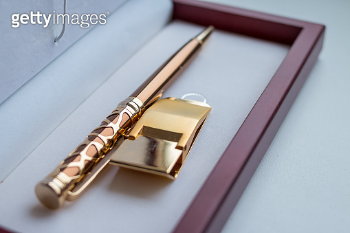 Open gift set. holder clip for money. stationery. wooden present box. golden money clip. A pen in a gift box isolated on white.fountain pen in wooden case made of mahogany, business concept