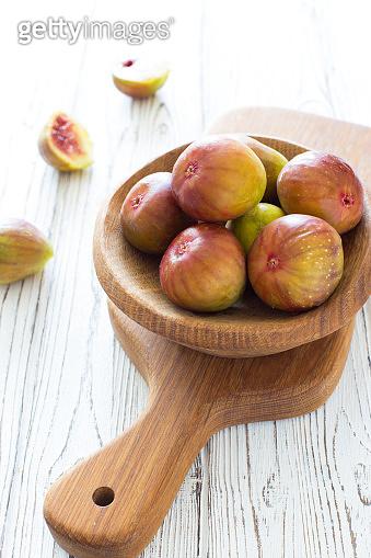 Ripe fresh figs in wood bowl