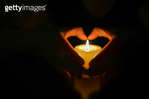 Hands protecting burning candle candlelight in darkness