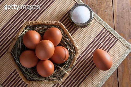 Several brown chicken eggs. Salt in salt shaker.