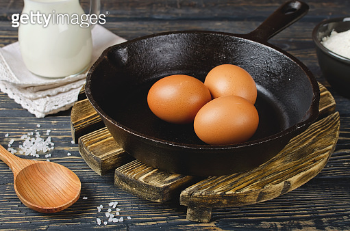 Whole raw eggs in a pan on a wooden table