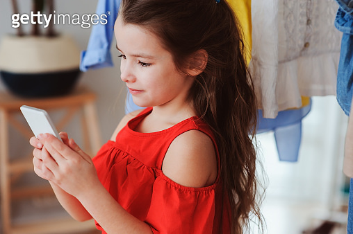 aa8fd0248560 cute little child girl choosing new modern clothes in her wardrobe ...