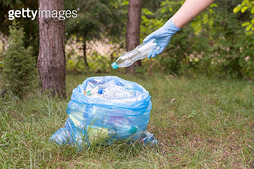 Picking up litter and putting it into a garbage bag