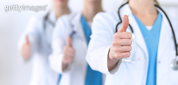 Groupe of medicine doctors show OK sign with thumb up close up. Success and high level service in health care, best treatment and customer loyalty and physical concept. Copy space for advertisement.