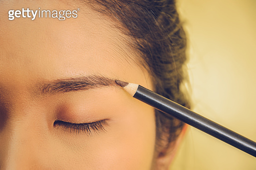 Beauty face of Asian woman by applying eyebrow pencil and smooth skin by cosmetics.