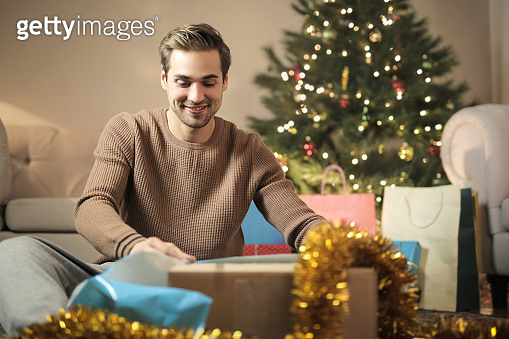 Guy wrapping Christmas gifts