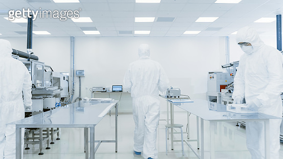 Scientist in Protective Suit Carries Case of Finished Product Through Laboratory. Workers in the Facility with Modern Industrial Machinery. Product Manufacturing Process: Pharmaceutics, Semiconductors, Biotechnology.