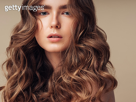 Young brown haired beautiful model with long, wavy, well groomed hair