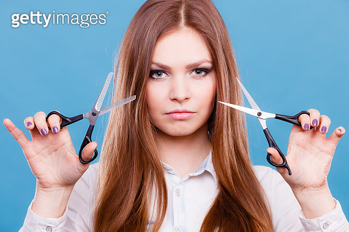 Young professional hairdresser with scissors.