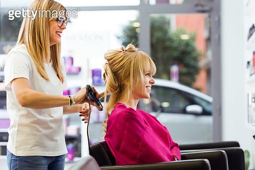 Hairdresser drying female customer's hair in beauty salon.