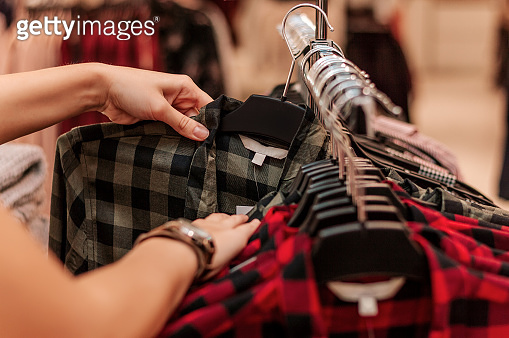 Buyer chooses a t-shirt in a boutique closeup.
