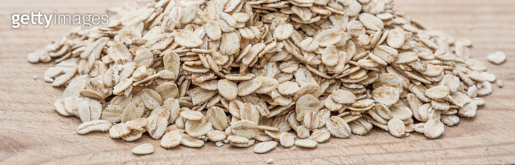 Rolled oats.  Granola, cereals or Oatmeal on white wooden old table. Healthy breakfast, copy space