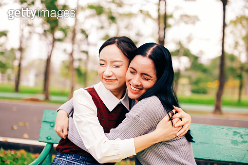 Two diverse ethnicities of Asian and Caucasian best female friends hugging and embracing each other in the park.