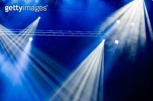 Blue light rays from the spotlight through the smoke at the theater or concert hall. Lighting equipment for a performance or show