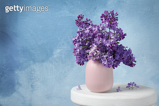 Vase with beautiful blossoming lilac on table against color background. Spring flowers