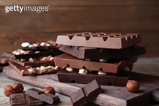 Different delicious milk and dark chocolate bars on table