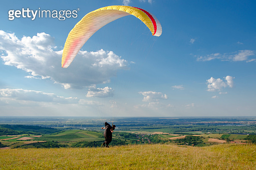 Man running with parachute on beautiful sunny day