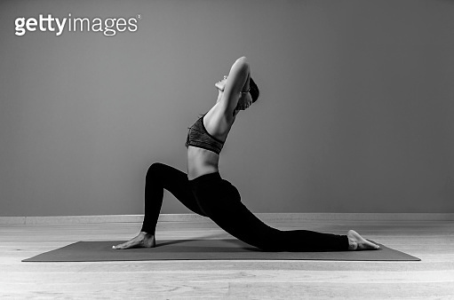 Attractive fit woman in yoga pose indoors