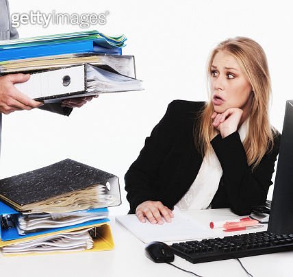 Overworked blonde office worker is shocked by extra work