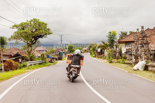 Men carry a stereo on a bike. Driver driving motorcycle through village.