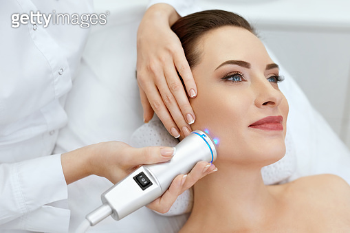 Face Skin Care. Woman Doing Blue Light Therapy At Beauty Clinic