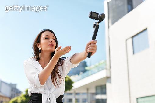 Woman Recording Video Blog On Camera On Street