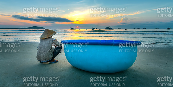 Old fisherman seated on a beautiful beach at dawn next to boat looking relatives fishing