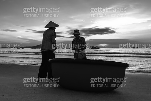 The elderly couple on a beautiful beach at dawn next to a basket boat looking to catch fishermen