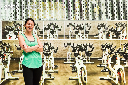 Beautiful female at the cycling studio with arms folded