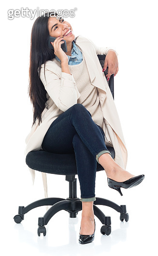 Attractive young latino female is sitting on a chair