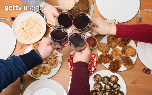 Hands with red wine toasting over served table with food. Happy friends or relatives enjoying dinner. Eating Concept.