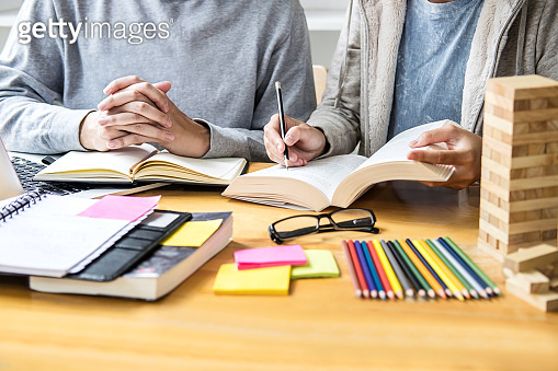 High school tutor or college student group sitting at desk in library studying and reading, doing homework and lesson practice preparing exam to entrance, education, teaching, learning concept