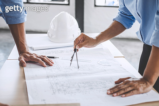 Hands of architect or engineer working on blueprint meeting for project working with partner on model building and engineering tools in working site, Construction concept
