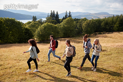 A group of five young adult friends smile while walking on a rural path during a mountain hike, side view